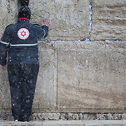 An Israeli emergency medical technician (EMT) prays as snow and rain fall at The Western Wall on January 7, 2015 in Jerusalem, Israel. (Photo by Elan Kawesch)