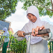 CAPTION: In addition to learning about the causes and effects of climate change in class, students are required to spend two to three hours a week implementing practical adaptation and mitigation solutions around school. In this picture, Dwi is installing a biopore outside her classroom. This takes less than an hour to complete, and the only tool required is a kind of long, T-shaped spade. By increasing the soil's re-absorption capacity, biopores play an effective role in reducing the risk of flooding. LOCATION: SMP N 7 School, Bandar Lampung, Indonesia. INDIVIDUAL(S) PHOTOGRAPHED: Dwi Wijayanti.