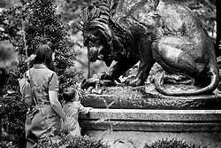 Mother and daughter play with a toy cat at the foot of the Lion Crushing a Serpent statue by artist. Antoine-Louis Barye, in Rittenhouse Square.