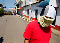 A man wearing mask stand it the street outside the mayors office Tuesday Sept. 11, 2007, Palin Guatemala. A angry mob took to the streets and went on to burn down the mayors office as well as his home in demonstration after and clash with local police on the previous day. Residents accuse the mayor of, among other things, of bussing voters for the elections on Sept. 9 2007.   (photo by/ Darren Hauck)..............