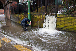© Licensed to London News Pictures. 25/02/2020. Shrewsbury, Shropshire, UK. A young man takes photos of watercascading over a wall. It starts to rain again as the River Severn levels continue to rise at Shrewsbury in Shropshire, UK causing severe flood disaster situation. Photo credit: Graham M. Lawrence/LNP