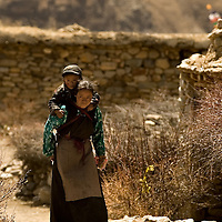 Nanka of 24 is carrying her son who is affected by the Kashin-Beck Disease, in the Lhasa river valley. Well know as well as the Big bone Disease,  One of the characteristics of this disease is that it affects the normal growth of the bones and disables the person to walk normally, and they stay short and remains with allot of troubles to walk normally..Narme, Tibet, China. April 14, 2007. Photo: Bernardo De Niz