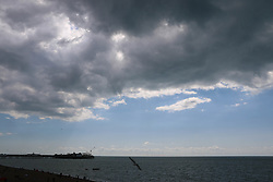 © Licensed to London News Pictures. 23/08/2014. Brighton, UK. Darl clouds hang over Brighton Beach at Brighton seafront today. Temperatures across the UK are expected to be low for the Bank Holiday weekend. Photo credit : Hugo Michiels/LNP