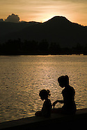 Silhouette along the Kampot River with Bokor Mountain in the background - Kampot is a small Cambodian provincial town where fishing is a major industry as well as pepper and salt.  The riverfront, actually an estuary, is the scene of much activity especially at dawn and sunset as it serves as a community focal point.