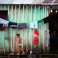 South America, Brazil, Amazon.  A young boy and a clothesline portray life on the Amazon.