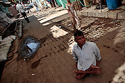 A man with legs not able to walk, makes his way across the cobbled road.  The slum of Cheetah Camp on the outskirts of Mumbai, India is a predominantly muslim community on living on the fringe while the city continues to grow.