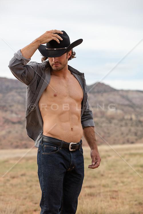 rugged muscular cowboy with an open shirt outdoors