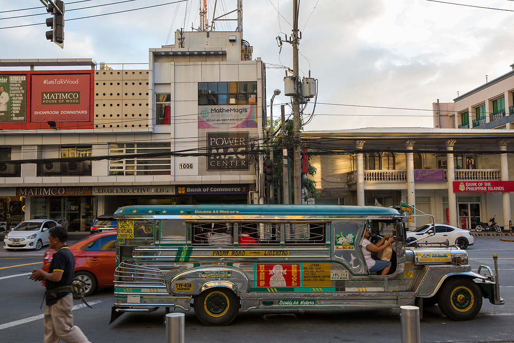 A jeepney stops on the side of the road in attempt to get customers on Antonio Arnaiz Ave, Makati, Metro Manila, Philippines. A jeepney, or 'dyipni' in Filipino, is a repurposed military jeep that is used as a free taxi in the Philippines. The high-rise building in the background is the Park Terraces building.  (photo by Andrew Aitchison / In pictures via Getty Images)