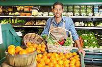 Portrait of man in supermarket with vegetable basket standing near oranges stall