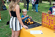 little boy playing an intelligence game at a day fair with a young adult woman watching