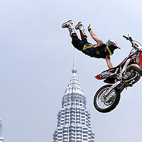 Jeremy Carter of the US perform an acrobatic stunt with his motorbike during the Asian X Games V in Kuala Lumpur, 24 January 2003. More than 200 athletes from 13 countries competing in five sport disciplines, skateboard, aggresive inline skate, bicycle stunt, wakeboarding and sport climbing during the events from 20 to 26 January. AFP PHOTO/Ahmad YUSNI