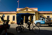 A bicycle taxi drives by the town hall in Baracoa, Cuba on Thursday July 10, 2008.