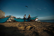 Commercial fisherman sit on their boat on the shore in Trincomalee, Sri Lanka, Wednesday, June 30, 2009. With the end of the 26 year old war between the Sri Lankan government and the LTTE, restrictions on fishing lanes have eased, allowing commercial fishers more time in the water to bring in their catch.