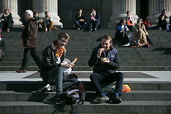London enjoys sunny weather this afternoon. People enjoy lunch in front of St.Pauls Cathedral. London, United Kingdom. Monday, 24th February 2014. Picture by Daniel Leal-Olivas / i-Images