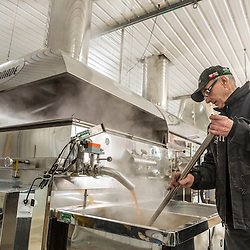 Rheaume Rodrique works the boiler in the Rodrique sugarhouse in Big Six Township, Maine.