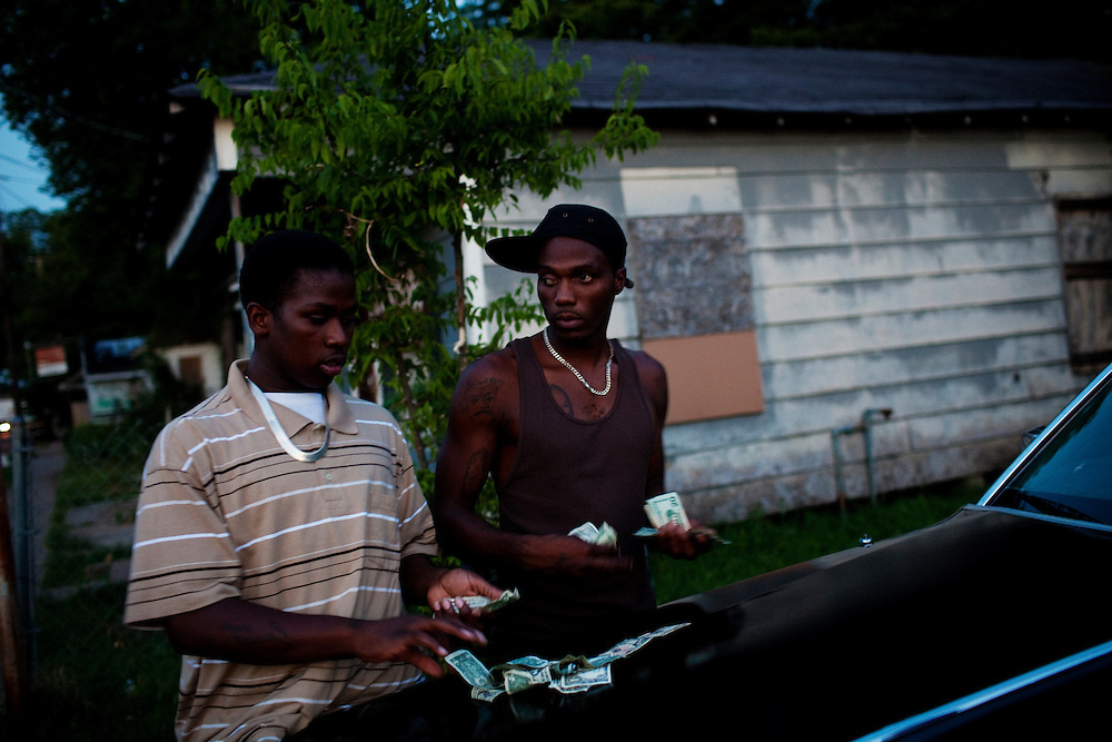 """Demetris """"Butta"""" Anderson, 18, and Winky Williams count money on a friend's car before a night of smoking, drinking and gambling in front of Hoover's Store in Baptist Town, Mississippi on July 2, 2010. Butta was shot and killed in October, becoming the third person in his family to be murdered."""