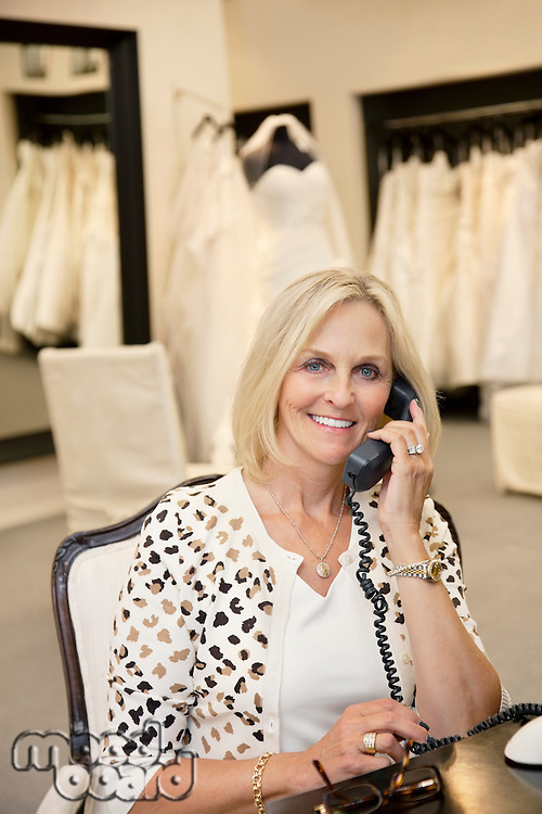 Portrait of a happy woman listening to telephone receiver in bridal store