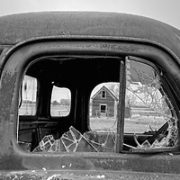 Broken glass in truck window with small wooden barn in background