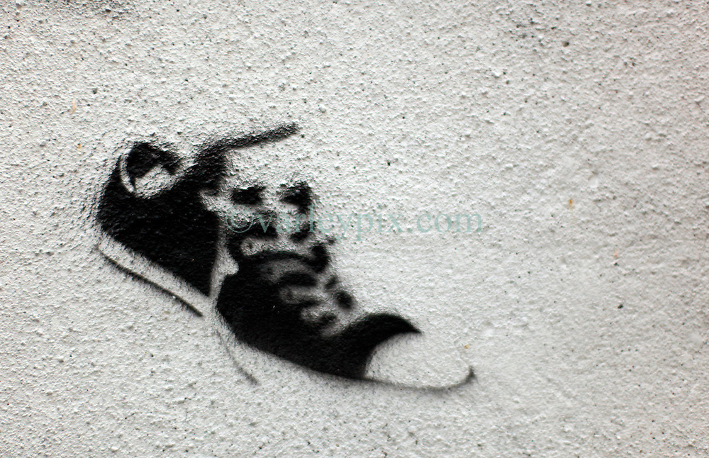 17 October 2013. New Orleans, Louisiana. <br /> Is it a Banksy? A shoe on a wall in alley where Lee Harvey Oswald and Judyth Vary Baker met close to the downtown Federal buildings in New Orleans. Banksy visited New Orleans in 2008 and various works attributed to him appeared at that time, yet sadly many have since disappeared. <br /> Photo; Charlie Varley<br /> varleypix.com