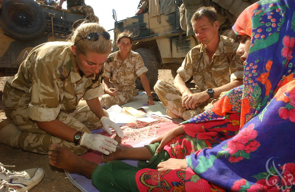 British field medic Corp. Cerianne Brown (l) and her medicla team treat local Afghan children June 21, 2002 during a humanitarian aid visit to the village of Dandar in Central Afghanistan. Britain announced the day before that it will withdraw the majority of its forces beginning the first week of July.