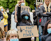 Lady protester with mask on and fight the power sign kneels with her fist in the air during black lives matter protest in Cardiff during the Black Lives Matter protest in Cardiff, Wales on 6 June 2020.