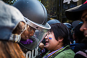 22 DECEMBER 2013 - BANGKOK, THAILAND:  A protestor tries to push past a Thai riot police officer at a roadblock preventing access to the home of caretaker Prime Minister Yingluck Shinawatra. Hundreds of thousands of Thais gathered in Bangkok Sunday in a series of protests against the caretaker government of Yingluck Shinawatra. The protests are a continuation of protests that started in early November and have caused the dissolution of the Pheu Thai led government of Yingluck Shinawatra. Protestors congregated at home of Yingluck and launched a series of motorcades that effectively gridlocked the city. Yingluck was not home when protestors picketed her home.    PHOTO BY JACK KURTZ