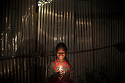 Jyoti, 12, is holding a candle during the celebrations for Diwali, the Hindu festival of lights, while standing in the front yard of her family's newly built home in Oriya Basti, one of the water-contaminated colonies in Bhopal, central India, near the abandoned Union Carbide (now DOW Chemical) industrial complex, site of the infamous '1984 Gas Disaster'.