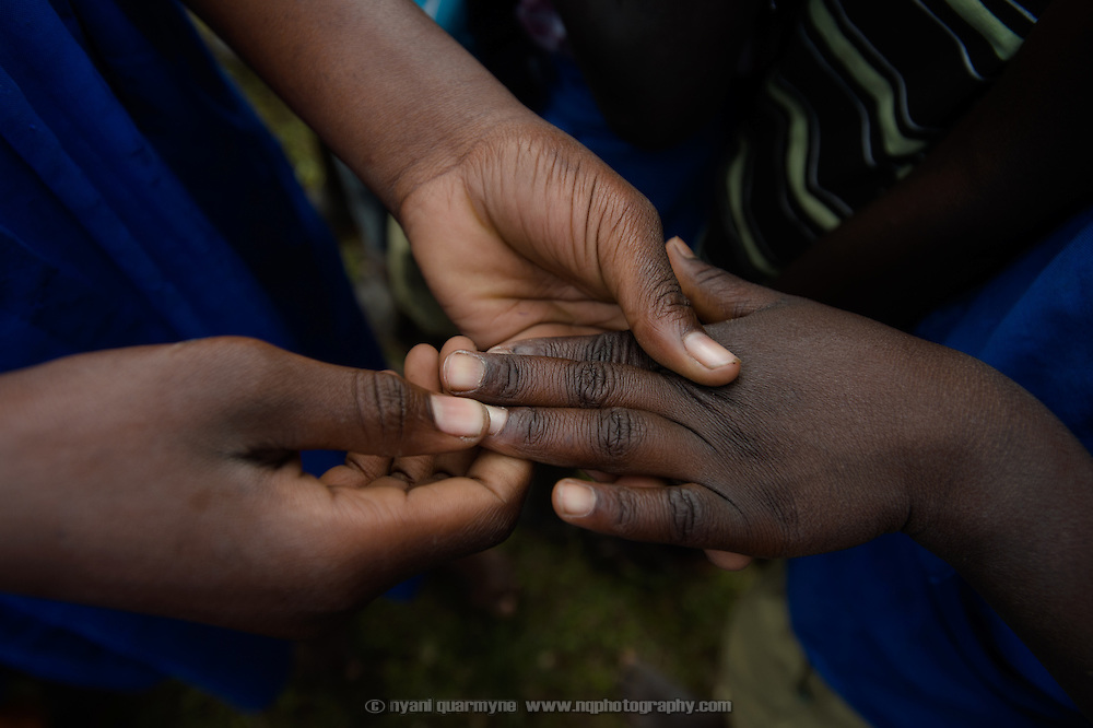 Health Prefect, Eseza Abbo (14), inspects her fellow students' fingernails for cleanliness at Agwait Primary School near Tororo in Eastern Uganda on 1 August 2014. The school participates in a Menstrual Health Management program supported by Plan International.