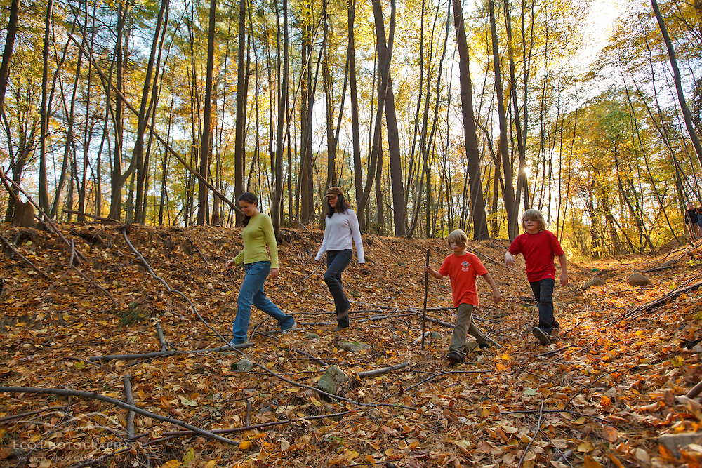 Two women and two nine year old boys walk a forest path at Elmwood Farm in Hopkinton, Massachusetts.