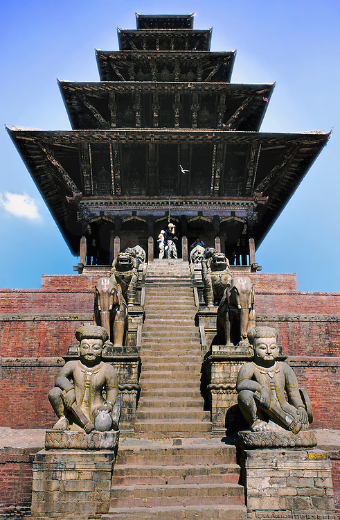 Frontal view of Nayatapola temple in Bhaktapur, looking up its steep staircase.  Built in 1708.   Seated statue of Shiva in the foreground.  All five levels of its pagoda-like roof are visible against the sky.
