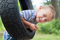 Portrait of a young boy winking while swinging on tire