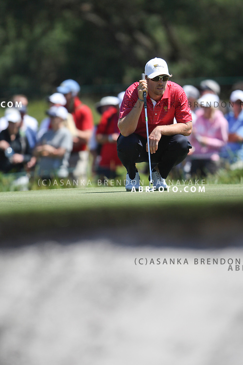 20 November 2011 : Hunter Mahan crouches to read a putt on the 2nd hole during the fifth-round Sunday Final round single ball matches at the Presidents Cup at the Royal Melbourne Golf Club in Melbourne, Australia. .