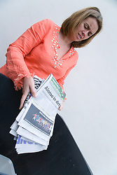 Woman putting old newspaper in recycling wheelie bin ready for collection,