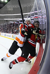 Jan 21; Newark, NJ, USA; Philadelphia Flyers defenseman Braydon Coburn (5) hits New Jersey Devils left wing Zach Parise (9) during the third period at the Prudential Center. The Flyers defeated the Devils 4-1.