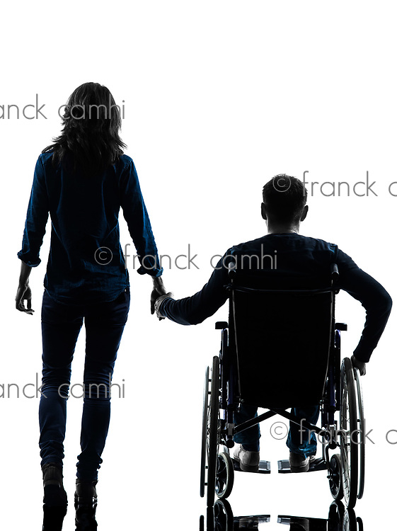 one handicapped man and woman holding hands in silhouette studio on white background