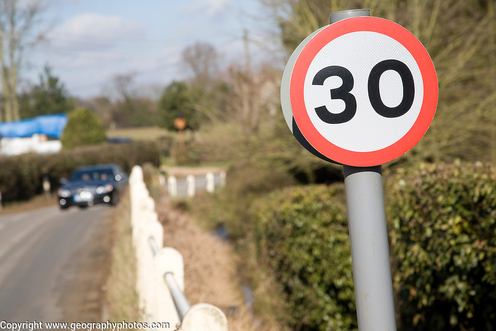 Thirty miles per hour road sign and car approaching