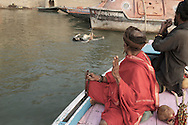 Rahm (R) and Baba G (L) pay respect while passing a death body in the Ganges River. Varanasi, India.