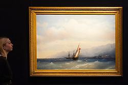 "© Licensed to London News Pictures. 25/11/2016. London, UK. A staff member views ""The Coast of Yalta"" by Ivan Aivazovsky (est. GBP 300-500k), at the preview of artworks from Sotheby's upcoming Russian sales in New Bond Street, where over three hundred works spanning several centuries will be offered. Photo credit : Stephen Chung/LNP"