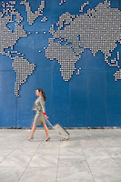 Business woman with suitcase walking past world map on wall