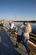 River cruise on Daugava river. Young lovers. TV-Tower in background.