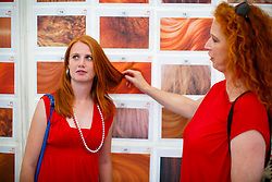 © Licensed to London News Pictures. 04/09/2016. Breda, The Netherlands. Ginger people match their hair colours and types with a chart as thousands of redheads fill a Dutch city Breda to celebrate International Redhead Day event in The Netherlands on Sunday, 4 September 2016. Every year natural redheads from more than 80 countries come together at 'Roodharigendag' annual weekend long festival to celebrate their ginger genes. The event also holds the world record for the largest number of natural redheads being in one place. Photo credit: Tolga Akmen/LNP