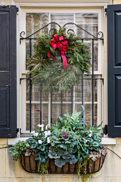 A Christmas wreath hands from a window of a historic home on the Battery in Charleston, SC.