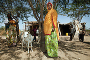 A woman from the village of Aada with the three goats she could buy thanks to a loan she received from the women's savings group.