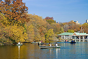 People rowing boats on the Lake in Central Park, New York City in Autumn with the Boathouse in background.