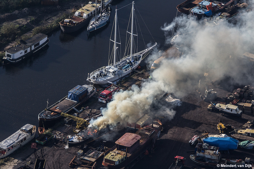 Luchtfoto van felle uitslaande brand op een schip van Gebroeders Los CMS Schepen aan de Greunsweg 21 te Leeuwarden. Het schip lag op de kant. Vermoedelijk ontstond de brand tijdens werkzaamheden aan het schip. De brandweer had de brand vrij snel met blusschuim onder controle. Tijdens de brand ontstond eerst een roetzwarte rookontwikkeling, die later overging in grijze rook. | Aerial view of raging fire on a ship of Brothers Los CMS in Leeuwarden, in the northern part of the Netherlands. The ship was on the side. Presumably arose the fire during work on the ship. The firefighters had the fire under control fairly quickly with fire-fighting foam. During the first fire was a sooty smoke, which later turned into gray smoke.