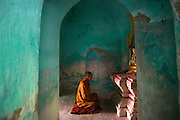 "A Buddhist monk meditates in prayer at one of the thousands of shrines in Amarapura, Burma's ""deserted city""."
