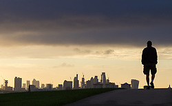 London, September 11 2017. A walker's figure is thrown into silhouette against the London skyline, seen from Primrose Hill, as a new day breaks over the city. © Paul Davey