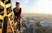 Hanging out on the roof of the world: Stomach-churning pictures of Russia's death-defying 'skywalkers' <br /> <br /> These photos are not for the faint-hearted or those with a fear of heights. They capture a man enjoying 'rooftopping', a hobby which has him living life literally on the edge.<br /> This striking series of photos show 'rooftopper' Kirill Oreshkin and his daredevil friends at the top of buildings, cranes, and construction sites – standing or even dangling from the top.<br /> The trend of rooftopping, or skywalking, has been documented in the last few years, and seems to be quite popular in Russia and Ukraine. It sees daredevils climb to the top of structures to take a unique, vertigo-inducing selfie.<br /> <br /> The young Moscow-based photographer completes his daredevil feats without a harness or safety net, but with a friend, who takes his picture.<br /> Despite the danger of his hobby, Oreshkin appears perfectly calm in the photos, even in the ones that show him hanging from structures by one hand.<br /> <br /> The feats of these daredevils are quite alarming. In one video posted on his personal website, Oreshkin's friend Mustang Wanted does chin-ups a few hundred metres above the ground in Kiev.<br /> <br /> Despite all appearances, the rooftoppers say they take what they do seriously. Mustang Wanted writes on his website:<br /> '[T]he following videos and photos feature stunts performed by professionals. I really insist that no one attempt to recreate or re-enact any stunt or activity performed on this site. Even if you're totally sure that you can do that, you are putting yourself in danger. So, please, don't try to recreate my stunts. I mean it!'<br /> ©Kirill Oreshkin/Exclsuivepix