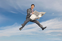 Business man reading newspaper mid-air outdoors