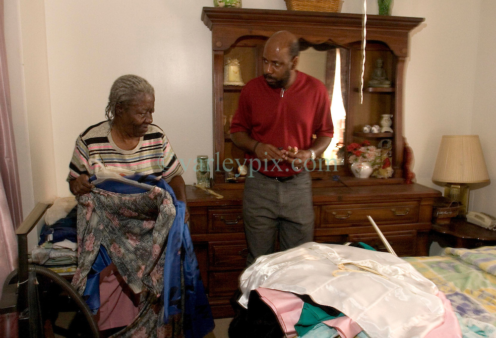 07 Oct, 2005.  New Orleans, Louisiana. Hurricane Katrina aftermath.<br /> 81 year old Rosella McKoy collects a few precious clothes from her bedroom at her home in the projects helped by her nephew, Kerry Young (41yrs) who gave her a ride back from Baton Rouge to check out her home in New Orleans. Her house was miraculously spared from the floods.<br /> Photo; ©Charlie Varley/varleypix.com
